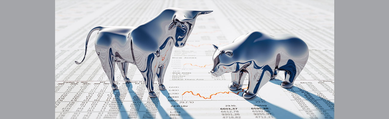 Silver Bull and Bear standing on a financial Newspaper.